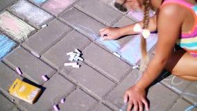 Sluit omhoog, een meisje in zonnebril, trek tekeningen met kleurpotloden op het asfalt, straattegels Een hete de zomerdag stock video