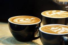 Sluit omhoog een mooie lattekunst bovenop een hete lattekoffie in een zwarte kop stock afbeeldingen