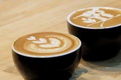 Sluit omhoog een mooie lattekunst bovenop een hete lattekoffie in een zwarte kop royalty-vrije stock afbeelding