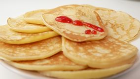 Sluit omhoog Een plaat van verse pannekoeken die met aardbeistroop water worden gegeven Het concept van het voedsel stock footage