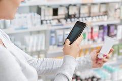 Sluit omhoog een vrouw die beeld van product in drogisterij nemen stock foto's