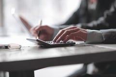 Sluit omhoog een zakenman gebruikt een calculator voor het berekenen van winsten stock foto