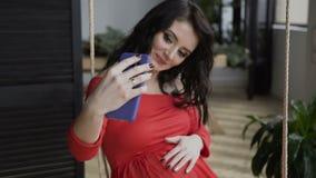 Sluit omhoog Een zwangere vrouw in een rode lange kleding die op de telefoon door het sociale netwerk spreken die draadloze vaj g stock videobeelden