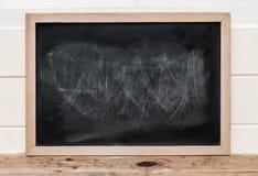 Sluit omhoog een zwart bord met houten kader op houten vloer Stock Foto