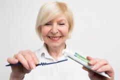 Sluit omhoog en snijd vuew van een vrouw die wat tandpasta op de tandenborstel zetten Zij wil haar tanden schoonmaken De dame is royalty-vrije stock afbeeldingen