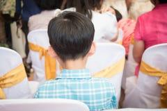 Sluit omhoog erachter van de kleine zitting van de gastjongen in vergaderzaal op ceremoniedag Stock Afbeeldingen