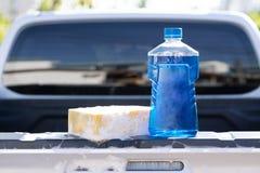 Sluit omhoog fles van autowasserettezeep met gele spons voor was, selectieve nadruk stock foto's