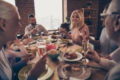 Sluit omhoog foto de grote toost van de familieverjaardag van de de ledenbroer van de wijnglazen de gouden drank van de de zuster stock foto