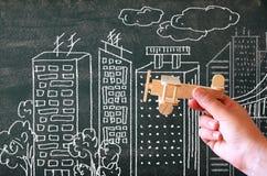 Sluit omhoog foto van de hand van de vrouw houdend houten stuk speelgoed vliegtuig tegen bord met stadsillustratie Royalty-vrije Stock Afbeeldingen