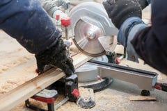 Sluit omhoog foto van de onherkenbare mens twee gebruikend hand elektrische zaagmolen om een deel van houten blok te snijden royalty-vrije stock afbeelding