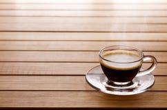 Sluit omhoog foto van een een koffiekop en schotel over een houten lijst met royalty-vrije stock foto's