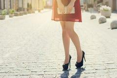 Sluit omhoog foto van mening van vrouwen` s de lange benen van zwarte van de stads de rode kleding royalty-vrije stock afbeelding