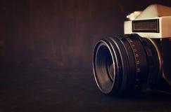Sluit omhoog foto van oude cameralens over houten lijst het gefiltreerde beeld is retro Selectieve nadruk Stock Afbeelding