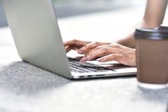 Sluit omhoog foto van vrouwenhanden typend op laptop bij straat stock afbeelding