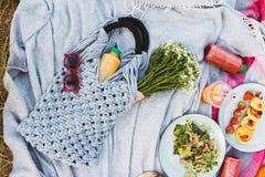 Sluit omhoog foto van zak met bloemen op picknickdeken heerlijk royalty-vrije stock afbeeldingen