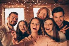 Sluit omhoog foto zich verzamelt de vriendengebeurtenis uit gedronken mensen maakt nemen selfies toont v-teken feestelijke nacht  royalty-vrije stock afbeelding