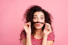 Sluit omhoog fotoportret van het leuke blije het gekscheren humoristisch lachen zij haar krul van de dameholding over mond die ge stock fotografie