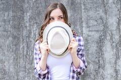 Sluit omhoog fotoportret van vrij mooi sluw sluw schuw dame verbergend gezicht achter headwear GLB-hoed kijkend opzij grijze B royalty-vrije stock afbeelding