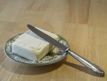Sluit omhoog gehele boterkubus op groene plaat met mes op houten t stock fotografie