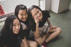 Sluit omhoog gelukgezicht van het Aziatische tiener ontspannen op schoolplaats royalty-vrije stock fotografie