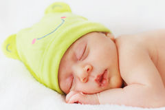 Sluit omhoog gelukkig nieuw babymeisje - geboren slaap in groene hoed Stock Fotografie