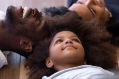 Sluit omhoog gelukkige Afrikaanse Amerikaanse familie samen liggend op warme vloer royalty-vrije stock foto's