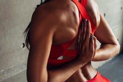 Sluit omhoog geschikte vrouw met wapens achter rug die uitrekkende oefeningen doen royalty-vrije stock foto's