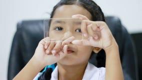 Sluit omhoog geschoten Aziatisch meisje in het Thaise kleuterschoolstudent eenvormige het gebruiken zelfde van het cleasglas zoal stock videobeelden
