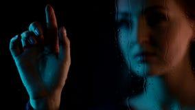 Sluit omhoog geschoten bij het droevige dromerige aantrekkelijke jonge vrouw wachten achter vochtig van het het glasvenster van d stock video