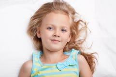 Sluit omhoog geschoten van blauw eyed klein kind bekijkt aangenaam camera, draagt toevallige nachthemden, heeft goede rust in bed royalty-vrije stock afbeelding