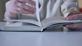 Sluit omhoog geschoten van de hand van de vrouw binnen lezend een boek stock footage