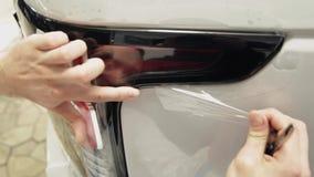 Sluit omhoog geschoten van de handen van een mens die de film van een witte auto pelt stock videobeelden