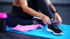 Sluit omhoog geschoten van de vrouwen` s voeten, die de schoenveters op de tennisschoenen verbindt stock videobeelden
