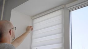 Sluit omhoog geschoten van een gewaagd manusje van alles die zonneblinden installeren op venster binnen stock videobeelden