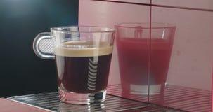 Sluit omhoog geschoten van een hand die een kop van koffie van espressomachine nemen stock footage