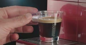 Sluit omhoog geschoten van een hand die een kop van koffie van espressomachine nemen stock video