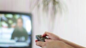 Sluit omhoog geschoten van een mannelijke hand die de TV-afstandsbediening houden en televisiekanalen veranderen stock video