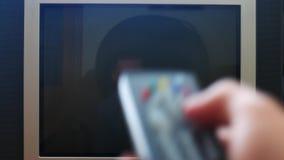 Sluit omhoog geschoten van een mannelijke hand die de TV-afstandsbediening houden en televisiekanalen zonder signaallawaai verand stock videobeelden