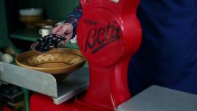 Sluit omhoog geschoten van een oude, retro, rode schaal en een verkoper die dingen weegt stock video