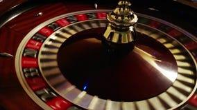 Sluit omhoog geschoten van een polshorloge met zich het witte wijzers bewegen De casinoroulette in motie met spinnewielbal, sluit stock footage