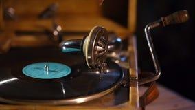 Sluit omhoog geschoten van een uitstekende grammofoon, de plaatrotaties en zendt geluiden van muziek uit stock videobeelden