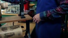 Sluit omhoog geschoten van een verkoper die een oud, retro document snijdt om suikergoed binnen te verpakken stock video