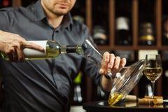 Sluit omhoog geschoten van ernstige meer sommelier gietende witte wijn in karaf Royalty-vrije Stock Foto