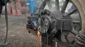 Sluit omhoog geschoten van fabrieksarbeider gebruikend scherpe toorts aan afzonderlijke metaaldelen van vrachtwagen` s wielen stock footage