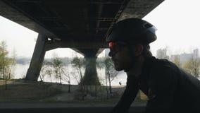 Sluit omhoog geschoten van fietser op een fiets Gebaarde fietser zwarte helm dragen en zonnebril die fiets met brug en rivier ber stock videobeelden