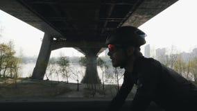 Sluit omhoog geschoten van fietser op een fiets Gebaarde fietser zwarte helm dragen en zonnebril die fiets met brug en rivier ber stock footage