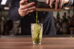 Sluit omhoog geschoten van gietende het basilicumcocktail van de barmanhand in een glas van schudbeker stock foto's