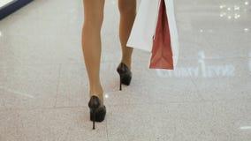 Sluit omhoog geschoten van jong vrouwenbeen die kleurrijke het winkelen zakken dragen terwijl het lopen in winkelcomplex op hoge  stock videobeelden