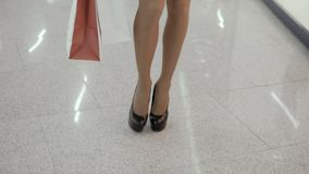 Sluit omhoog geschoten van jong vrouwenbeen die kleurrijke het winkelen zakken dragen terwijl het lopen in winkelcomplex op hoge  stock video