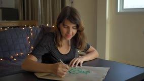 Sluit omhoog geschoten van jonge vrouwenkalligraaf die op een document zak schrijven gebruikend het van letters voorzien techniek stock videobeelden